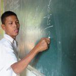 boy writing on blackboard