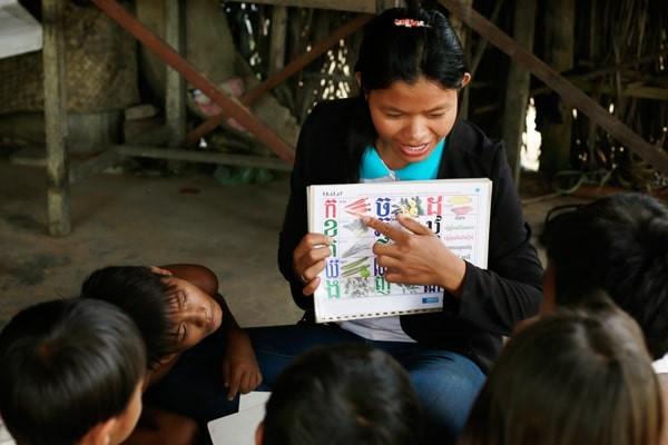 volunteer teaches kids Khmer alphabet
