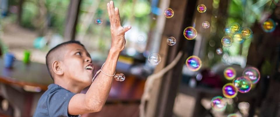boy catches bubbles