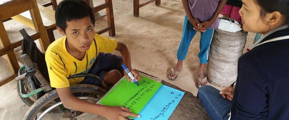 volunteer helps boy write