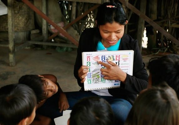 volunteer teaches kids Khmer alphabet